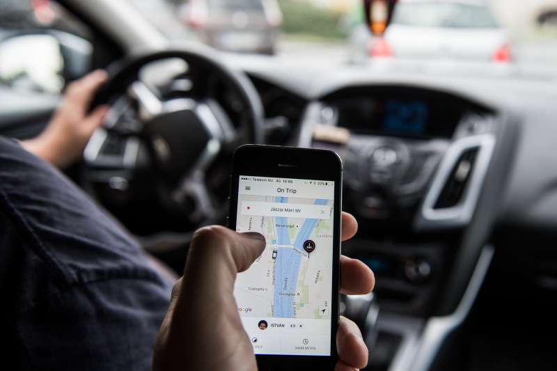 A passenger holds an iPhone displaying the Uber car service taxi application journey progress screen in Budapest, Hungary, on Wednesday, July 13, 2016.