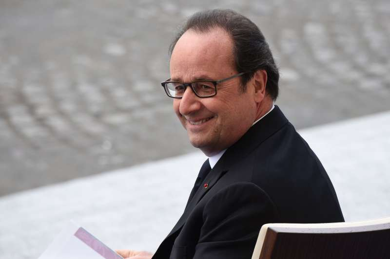 French President Francois Hollande smiles as he attends  the annual Bastille Day military parade on the Champs-Elysees avenue in Paris on July 14, 2016.