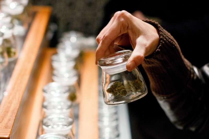A customer holds a sample bud of marijuana at Amazon Organics, a pot dispensary in Eugene, Ore., Oct. 1, 2015.
