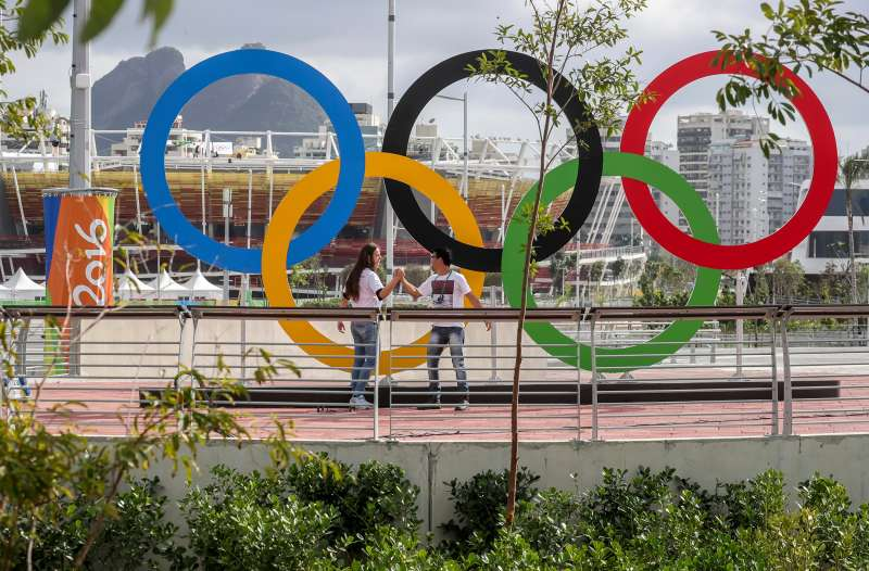 Young people stand in front of the Olympic Rings in Olympic Park in Rio de Janeiro,Brazil, 28 July 2016. The 2016 Olympic Games will take place in Rio de Janeiro from 05 to 21 August 2016.