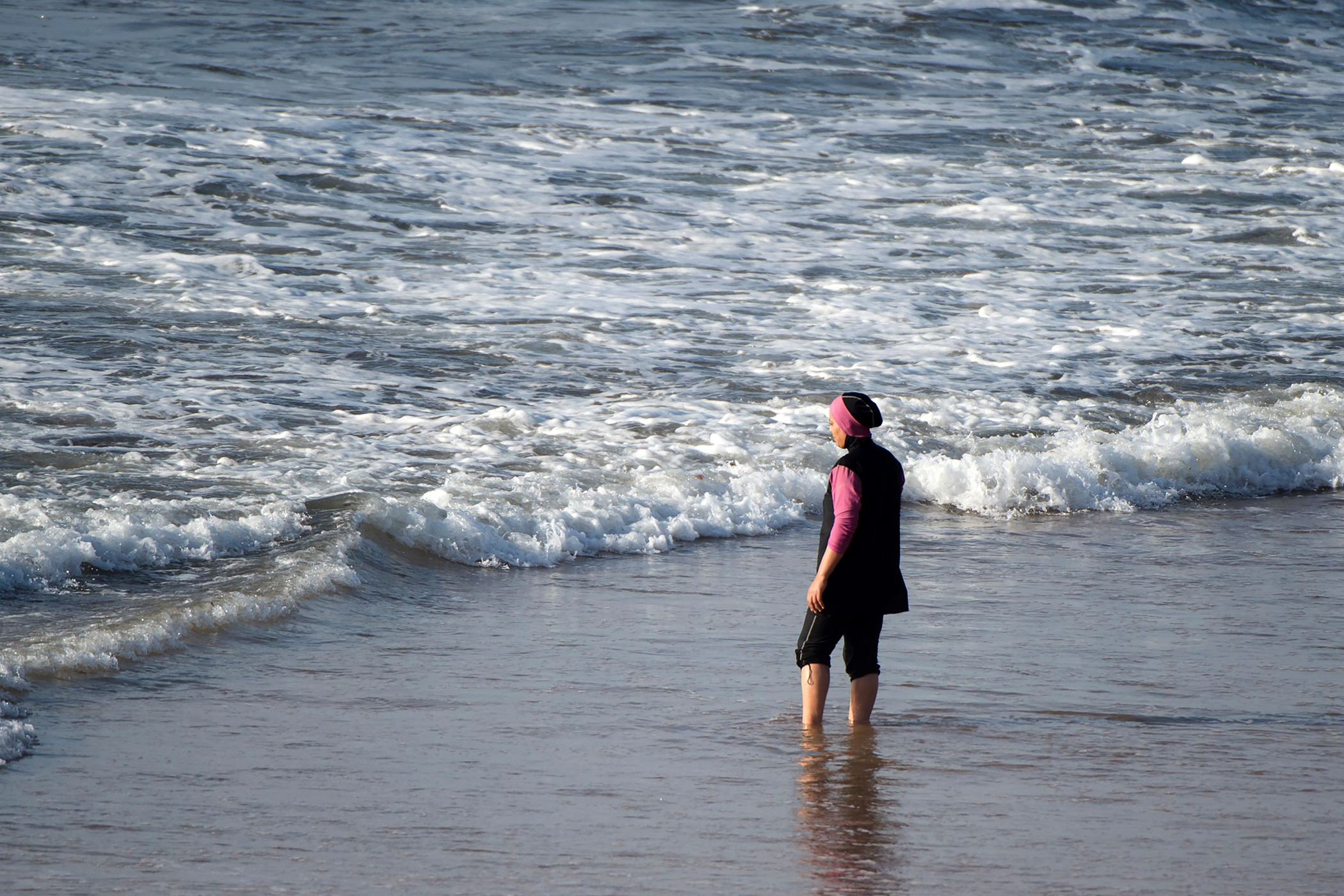 A woman wearing a  burkini , a full-body swimsuit designed for Muslim women.