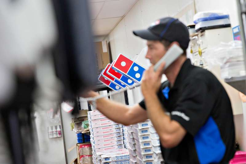 An employee takes a customer's order on the phone at a Domino's Pizza Inc. restaurant in Rantoul, Illinois, U.S., on Thursday, Oct. 8, 2015.