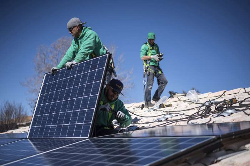 Workers secure solar panels to a rooftop during a SolarCity Corp. residential installation in Albuquerque, New Mexico, on Feb. 8, 2016.