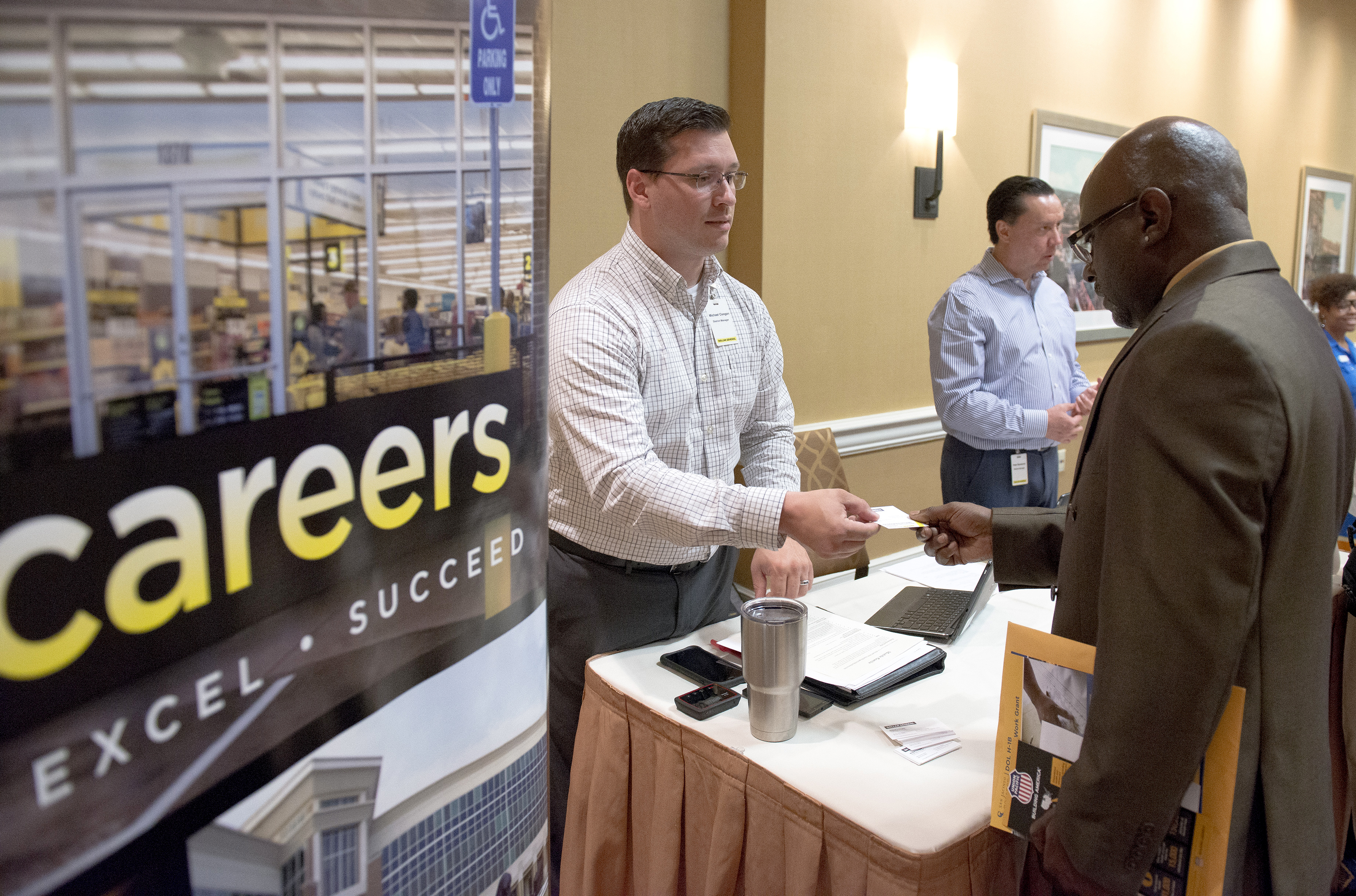 A Dollar General Corp. representative speaks to a job seeker during the Best Hire Career Fair in Houston, Texas, U.S., on Thursday, July 7, 2016.