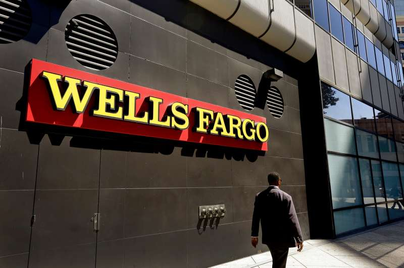 In this July 14, 2014, file photo, a man passes by a Wells Fargo bank office in Oakland, Calif. Regulators announced Thursday, Sept. 8, 2016, that Wells Fargo is being fined $185 million for illegally opening millions of unauthorized accounts for their customers in order to meet aggressive sales goals.