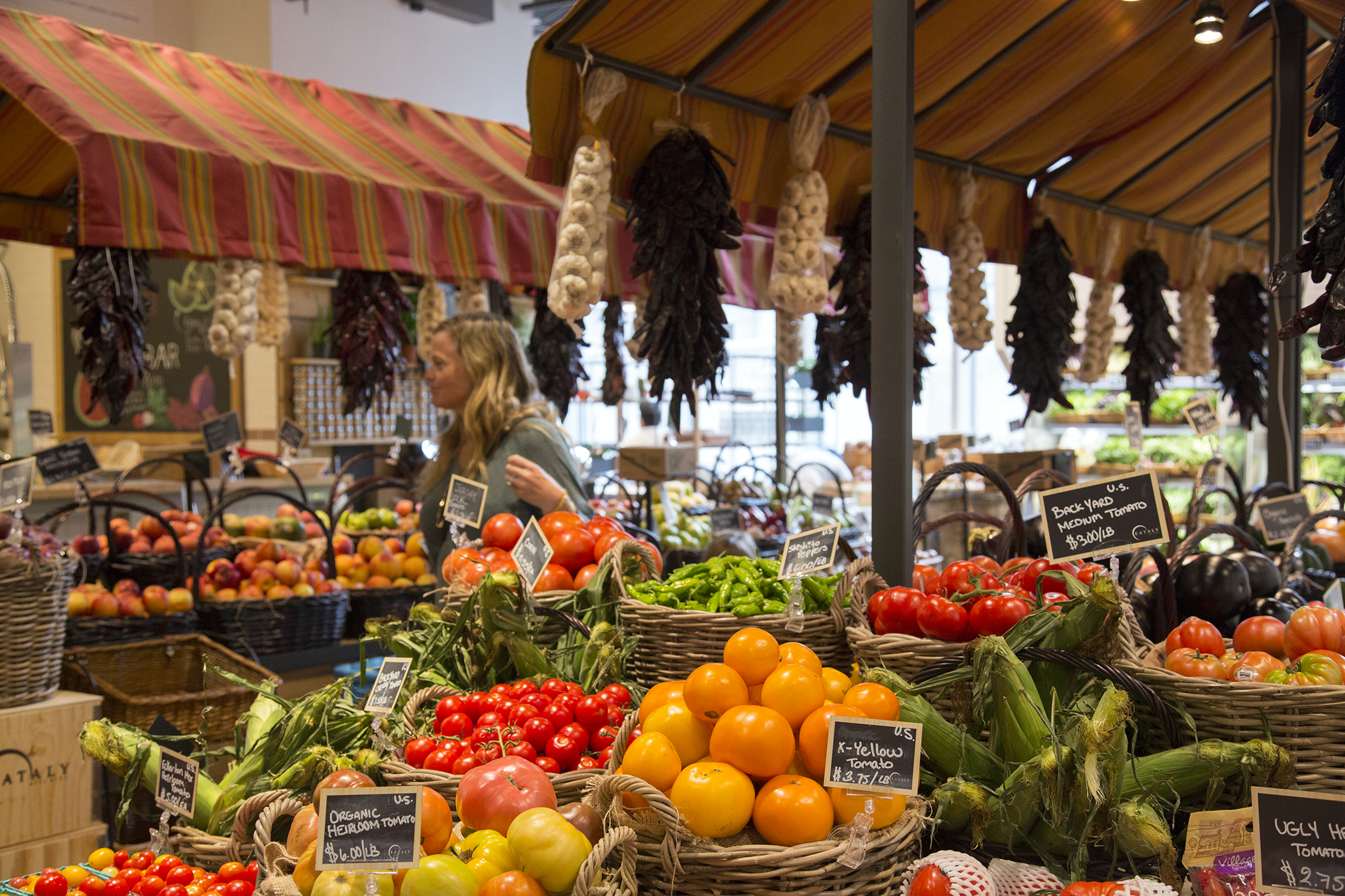 A woman selects fresh produce inside Eataly, Westfield World Trade, New York.