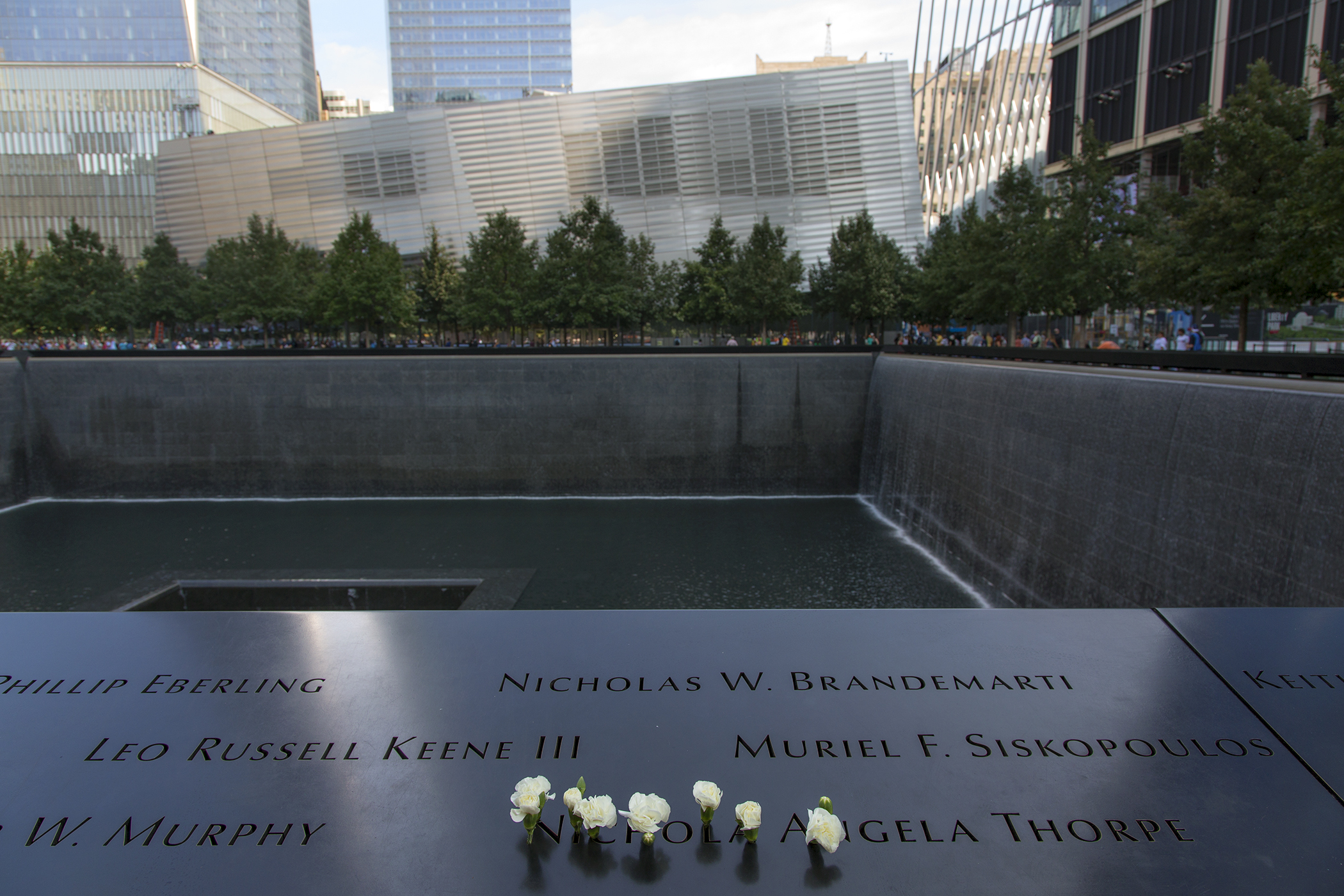 The names of victims of the September 11 terrorist attacks are engraved into the rim of one of the twin black granite reflecting pools at the September 11 Memorial and Museum, New York.