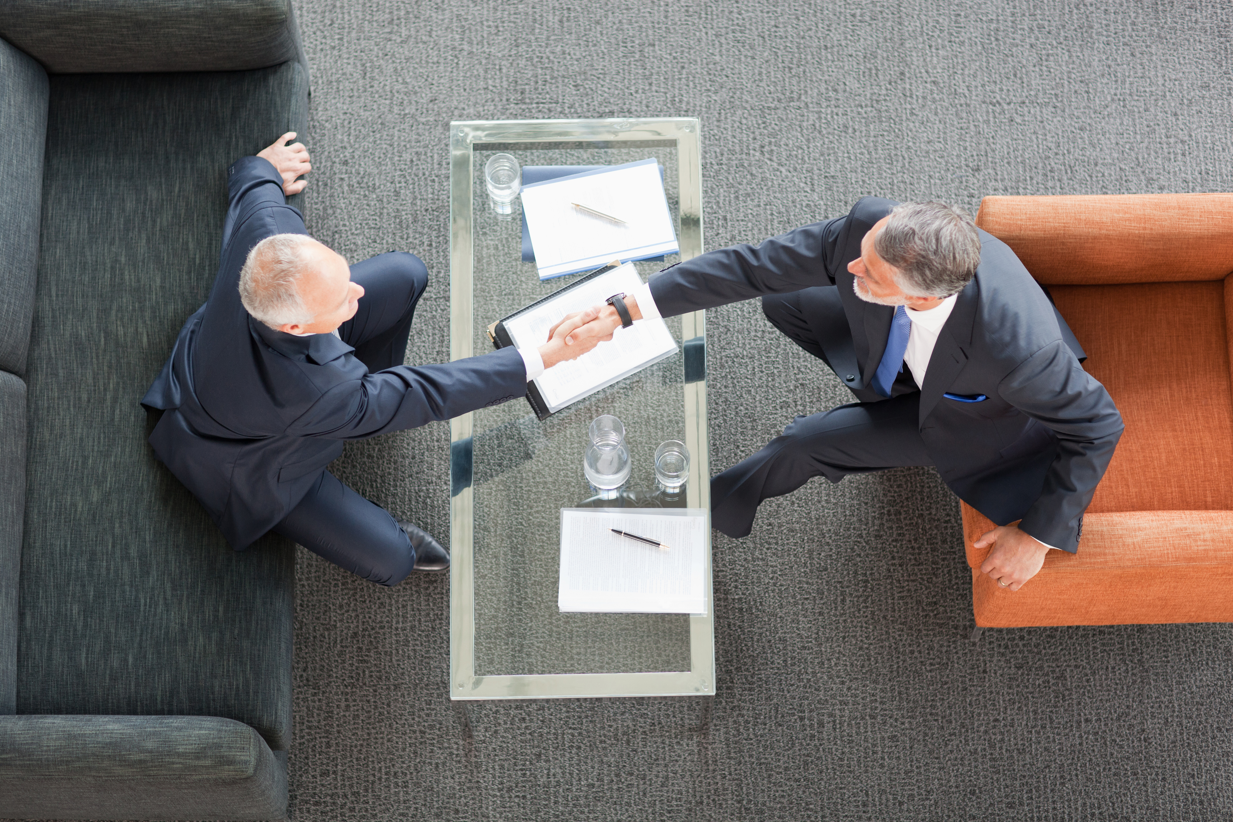 Businessmen shaking hands across coffee table in lobby