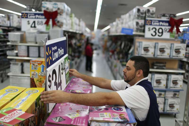 Jaime Vado fixes a display in the aisle at a Walmart store in Miami, Florida.