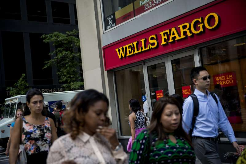 Pedestrians pass in front of a Wells Fargo & Co. bank branch in New York, U.S., on Tuesday, July 12, 2016.