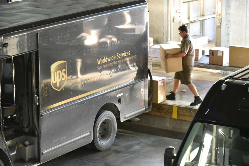 A United Parcel Service Inc. (UPS) driver loads packages onto a delivery truck at the company's Latin America and Caribbean sorting facilities at Miami International Airport in Miami, Florida, U.S., on Friday, Aug. 5, 2016.