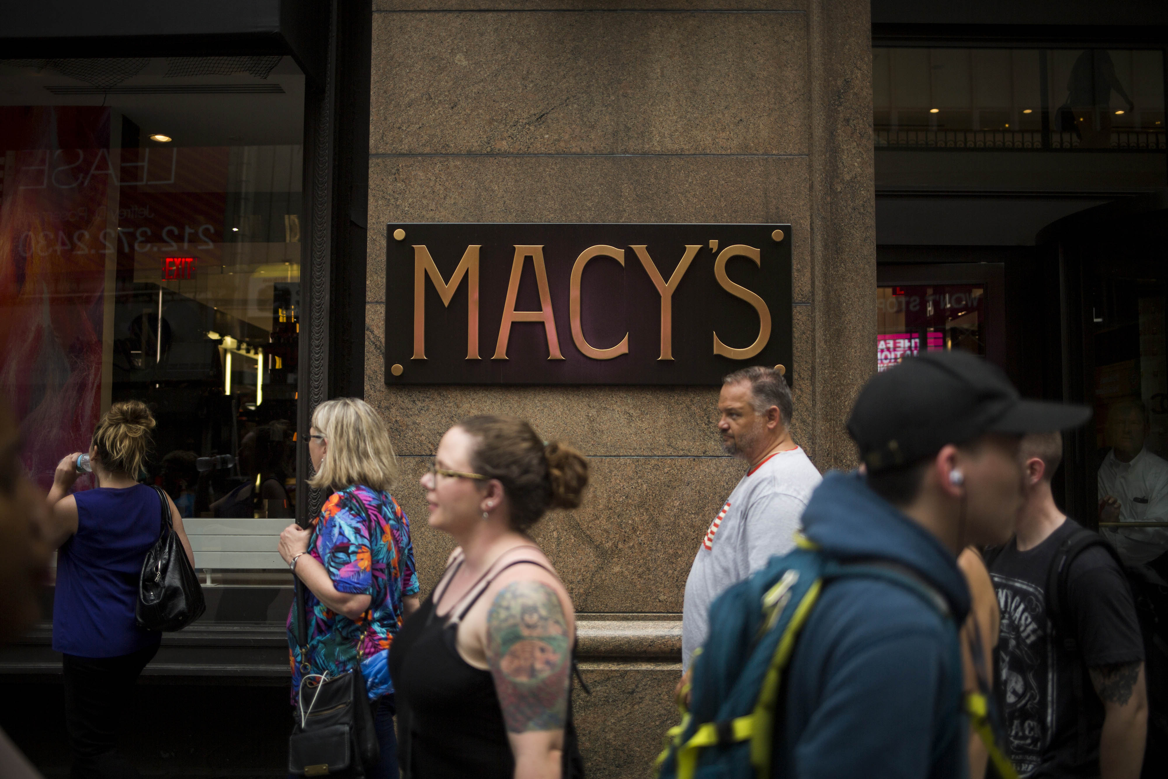 Pedestrians walk past a Macy's store in New York, U.S., on Thursday, Aug. 11, 2016.