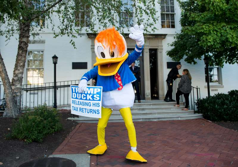 A man in a duck costume waves in front of the Republican National Committee headquarters in Washington on Tuesday, Sept. 13, 2016. The unidentified man in the costume holds a sign calling on Donald Trump to release his tax returns.