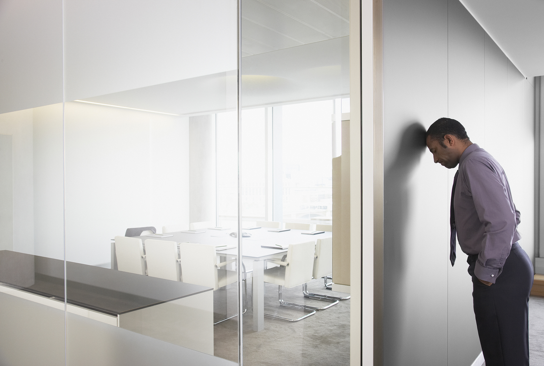 Businessman leaning on corridor wall