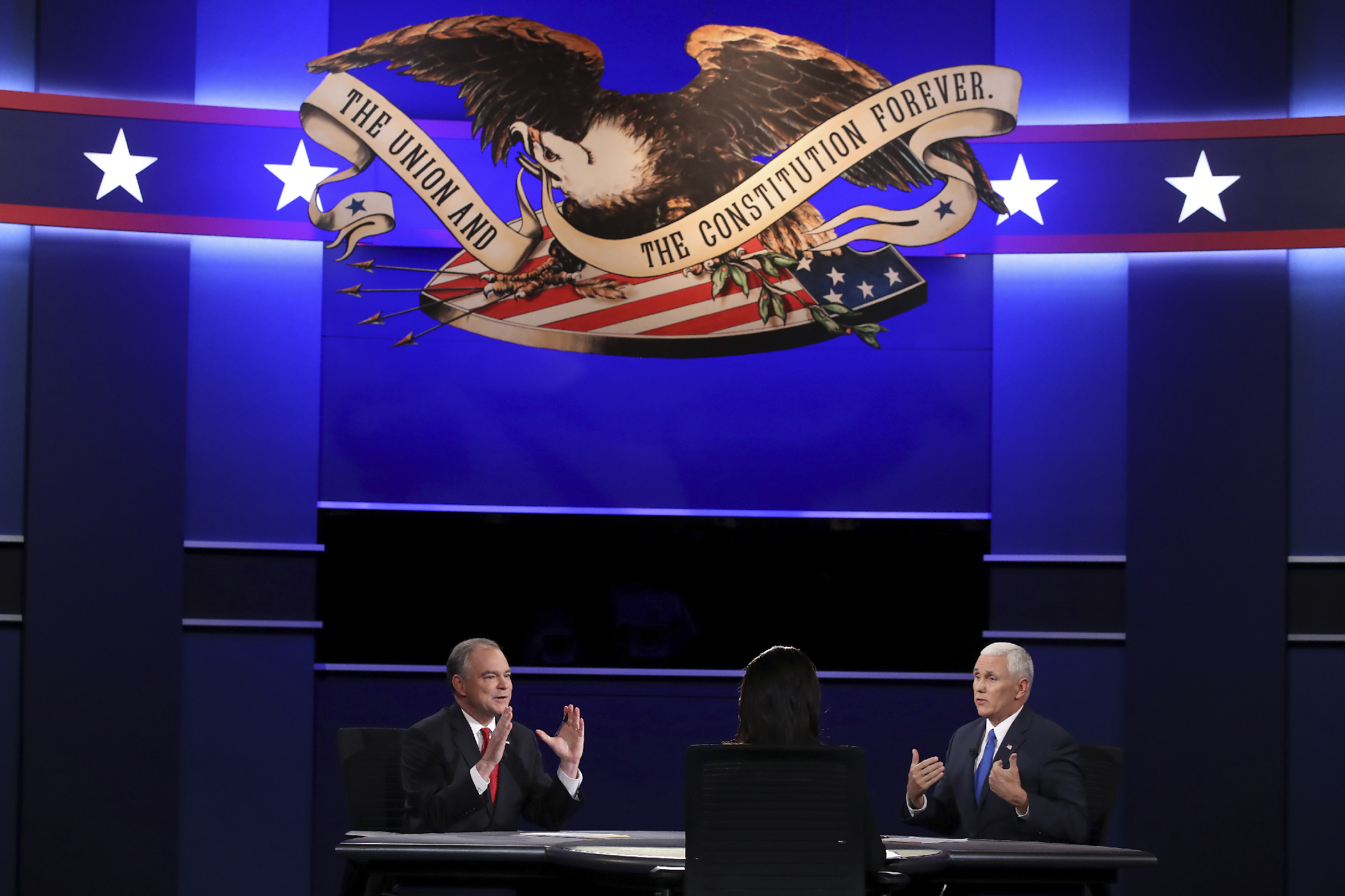 Democratic vice presidential nominee Tim Kaine (L) and Republican vice presidential nominee Mike Pence (R) speak as debate moderator Elaine Quijano (C) listens during the Vice Presidential Debate at Longwood University on October 4, 2016 in Farmville, Virginia.  This is the second of four debates during the presidential election season and the only debate between the vice presidential candidates.