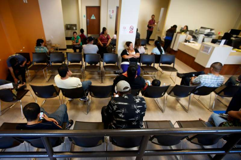 Patients sit in the waiting room at the St. John's Well Child and Family Center in Los Angeles, Calif.