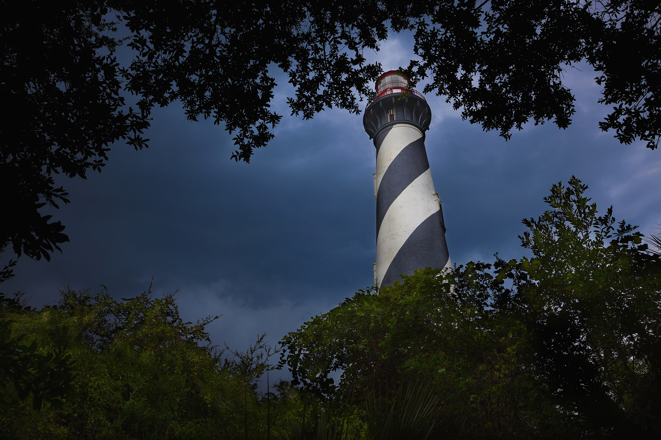 Lighthouse viewed through the trees and vegetation with dark and moody clouds in the sky; St. Augustine, Florida