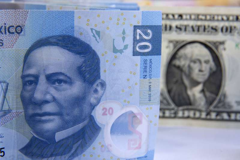 Mexican Peso bills are arranged for a photograph with a U.S. one dollar bill in Mexico City, Mexico, on January 27, 2016.