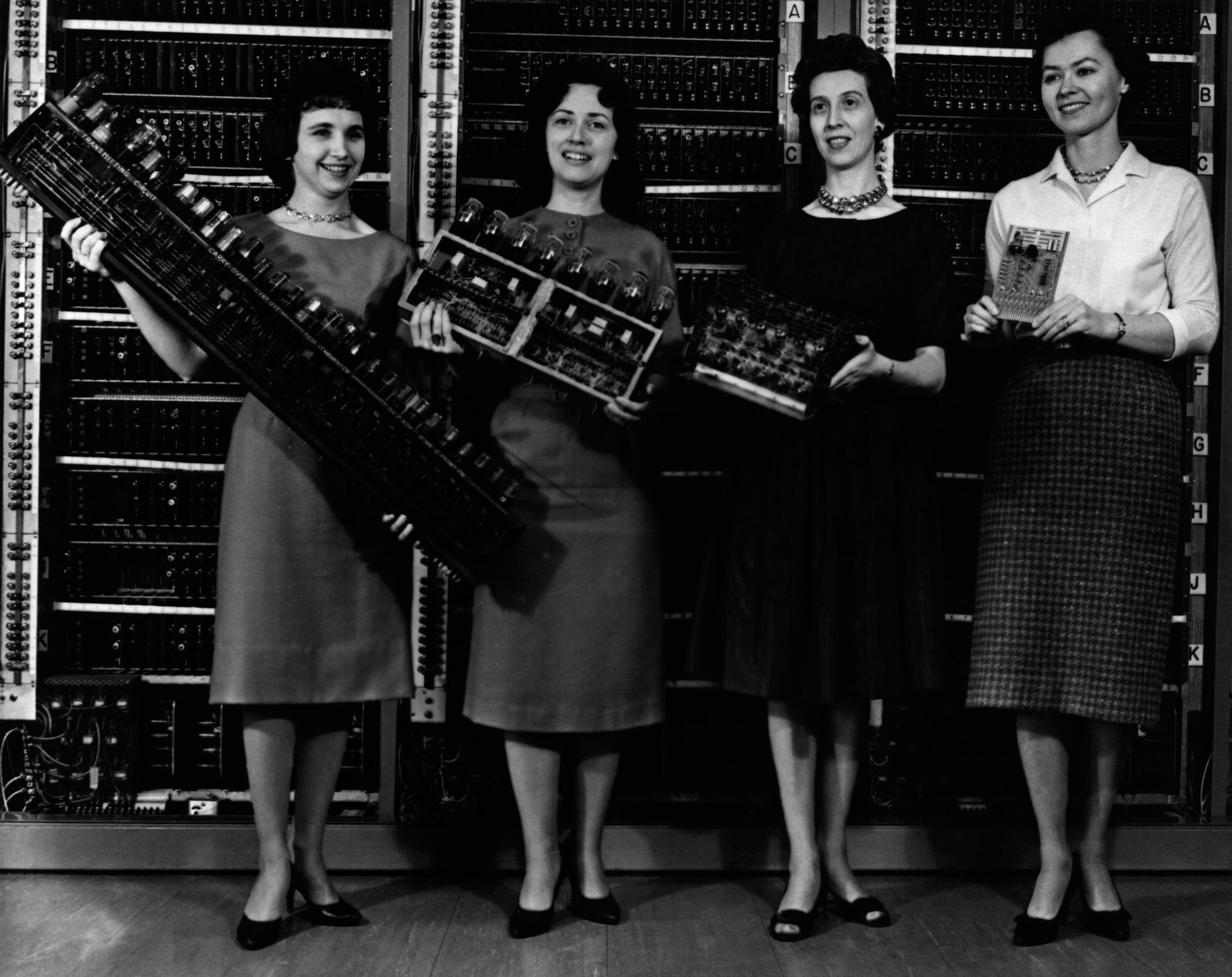 Women holding the first four computer circuit boards.