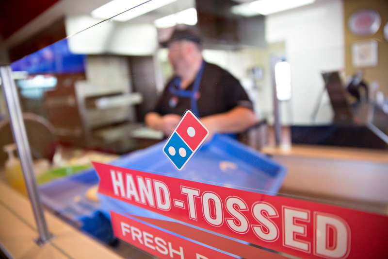 A hand-tossed sign stands in front of an employee preparing a customer's order at a Domino's Pizza Inc. restaurant in Rantoul, Illinois, U.S., on Thursday, Oct. 8, 2015.