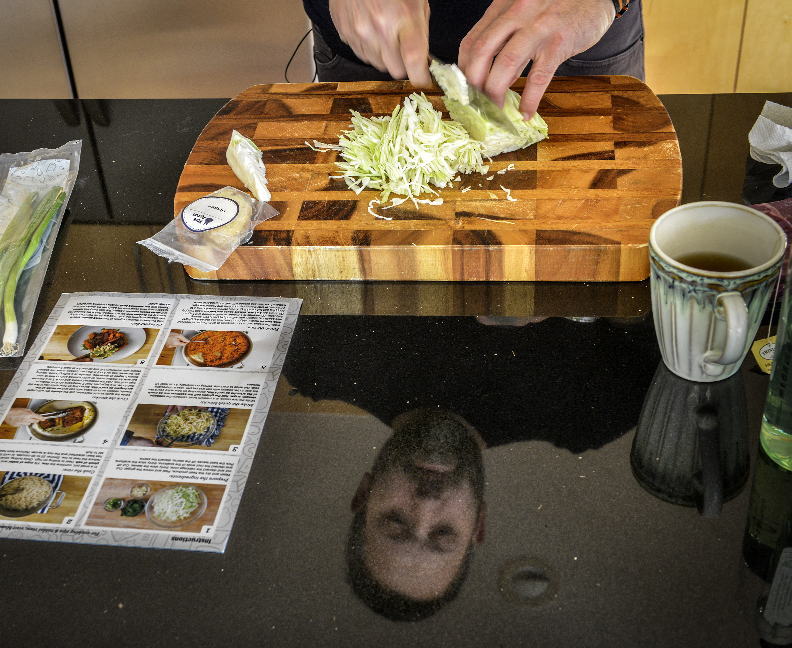 Chef Mike Isabella, reflected in his shiny black work surface, prepares a meal sent to him by Blue Apron, the online meal delivery service, in his home kitchen on December, 04, 2015 in Washington, DC.