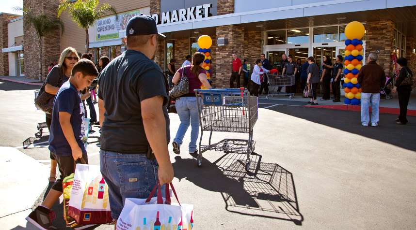 Shoppers carry their purchases as crowds wait in line to get into Aldi food market  during the grand opening  on March 24, 2016 in Moreno Valley, California. Aldi is opening its first 8 stores in Southern California.