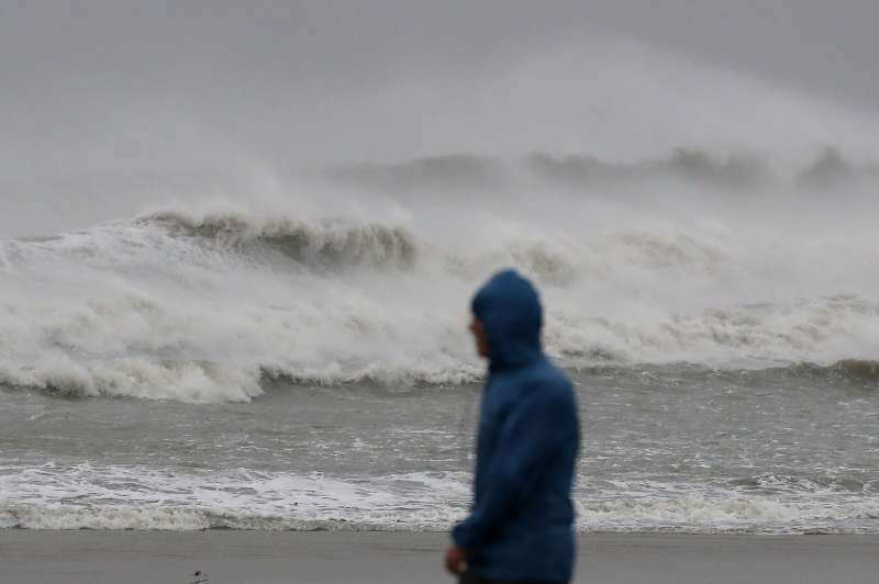 A man walks past heavy surf caused by Hurricane Matthew, October 7, 2016 on Cocoa Beach, Florida. Hurricane Matthew passed by offshore as a catagory 3 hurricane bringing heavy winds and minor flooding.