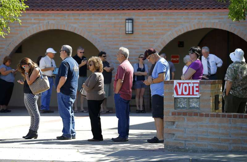 In this March 22, 2016 photo, voters wait in line to cast their ballot in Arizona's presidential primary election in Gilbert, Ariz. New ID requirements.