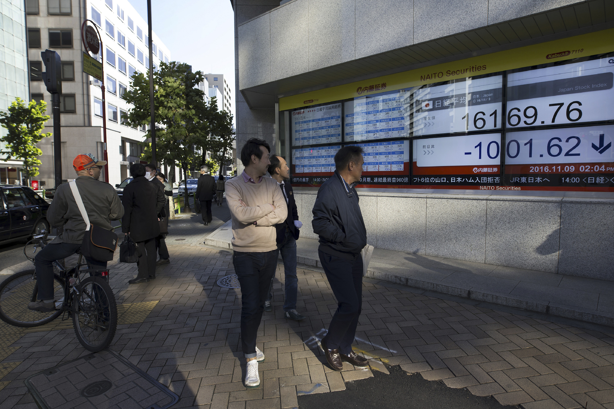 Pedestrians look at an electronic stock board displaying the Nikkei Stock Average outside a securities firm in Tokyo on Nov. 9, 2016. The yen strengthened against the U.S. dollar, which will make it more difficult for Japan to fight off its ongoing inflation problem.