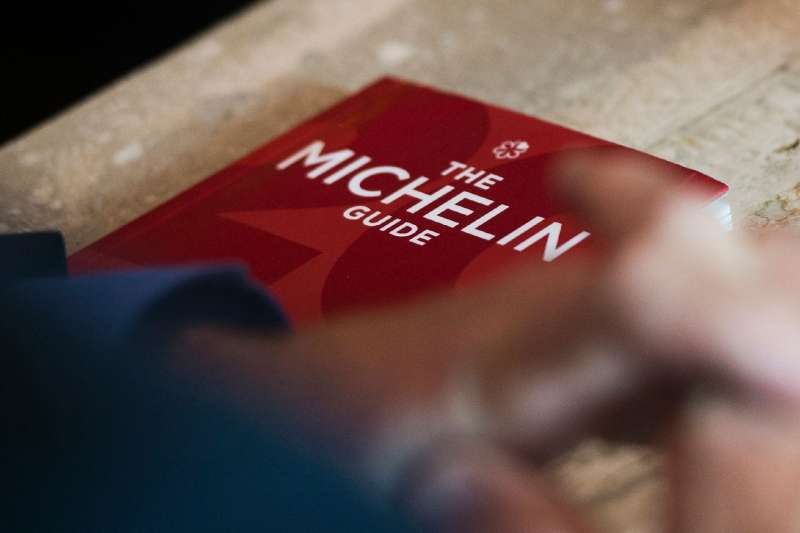 Michael Ellis from Michelin poses with the Michelin guide book at a restaurant in Washington, DC on October 12, 2016.