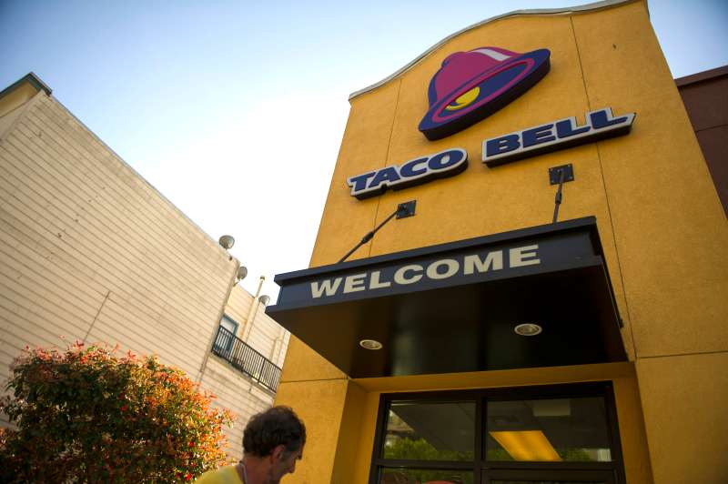 A pedestrian walks past a Taco Bell Corp. logo seen on the facade of a restaurant in San Francisco, California.