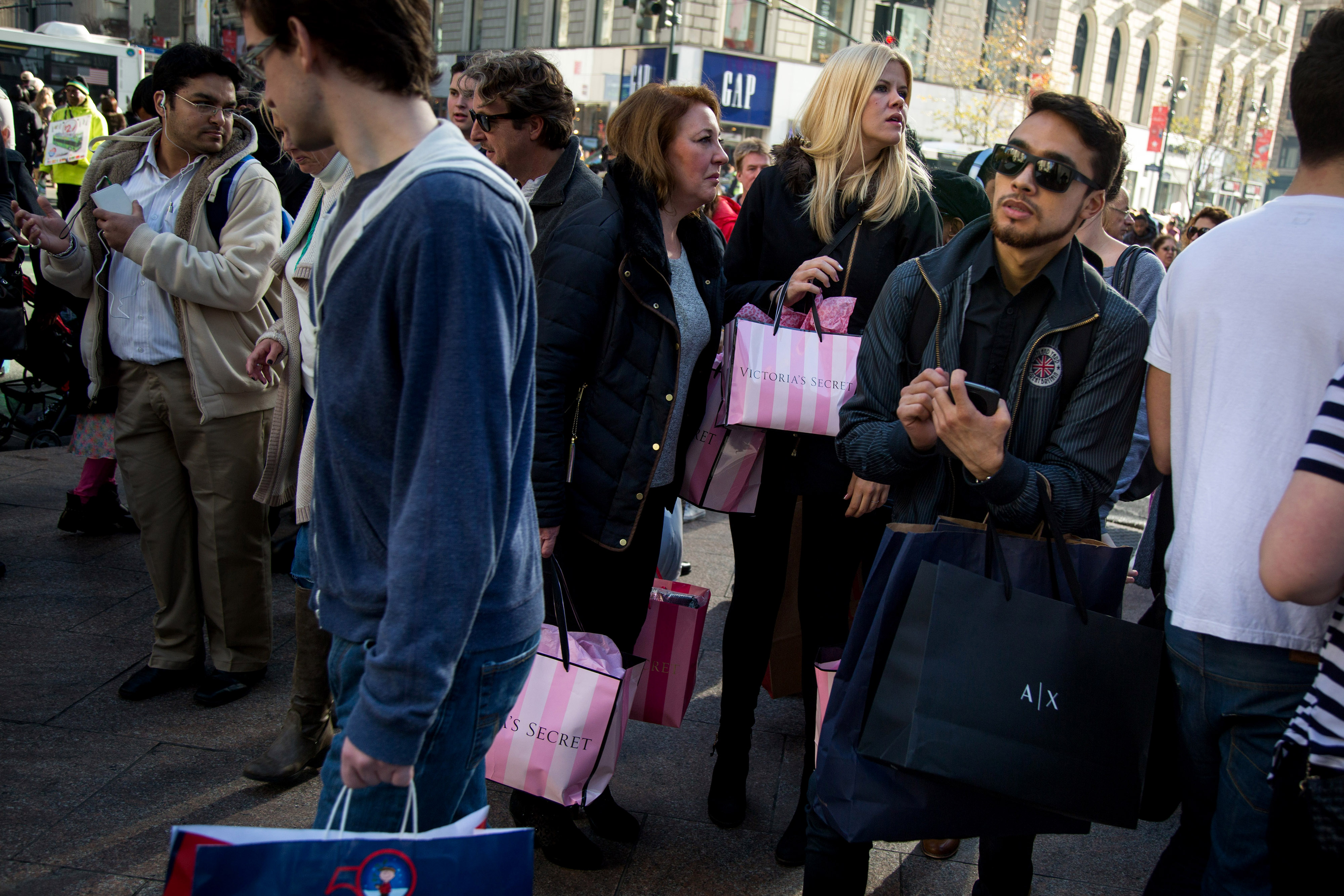 Pedestrians carry shopping bags on Black Friday through Herald Square in New York, U.S., on Friday, Nov. 27, 2015.