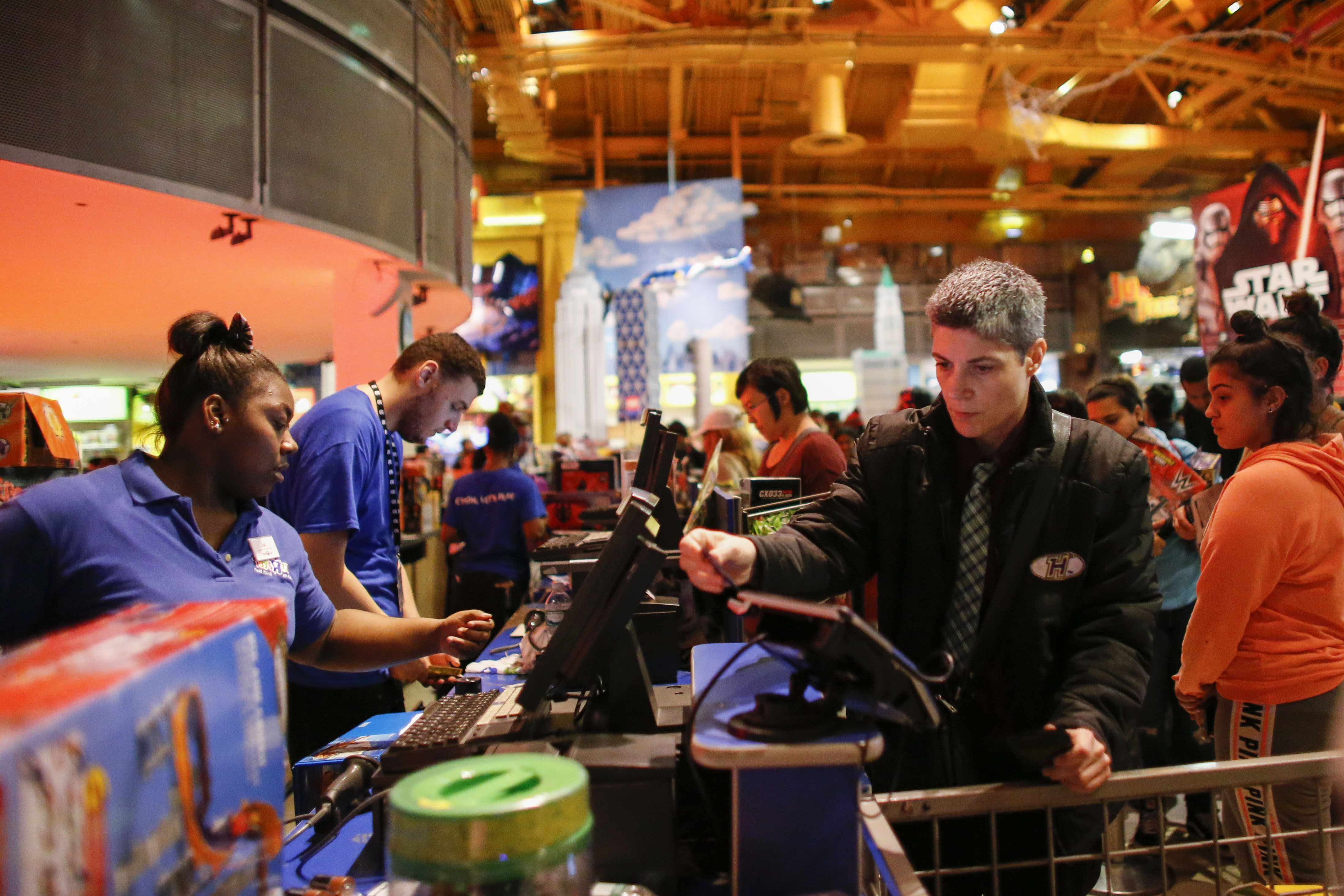 Shoppers pay for items at a Toys R Us store on December 24, 2015 in New York City.