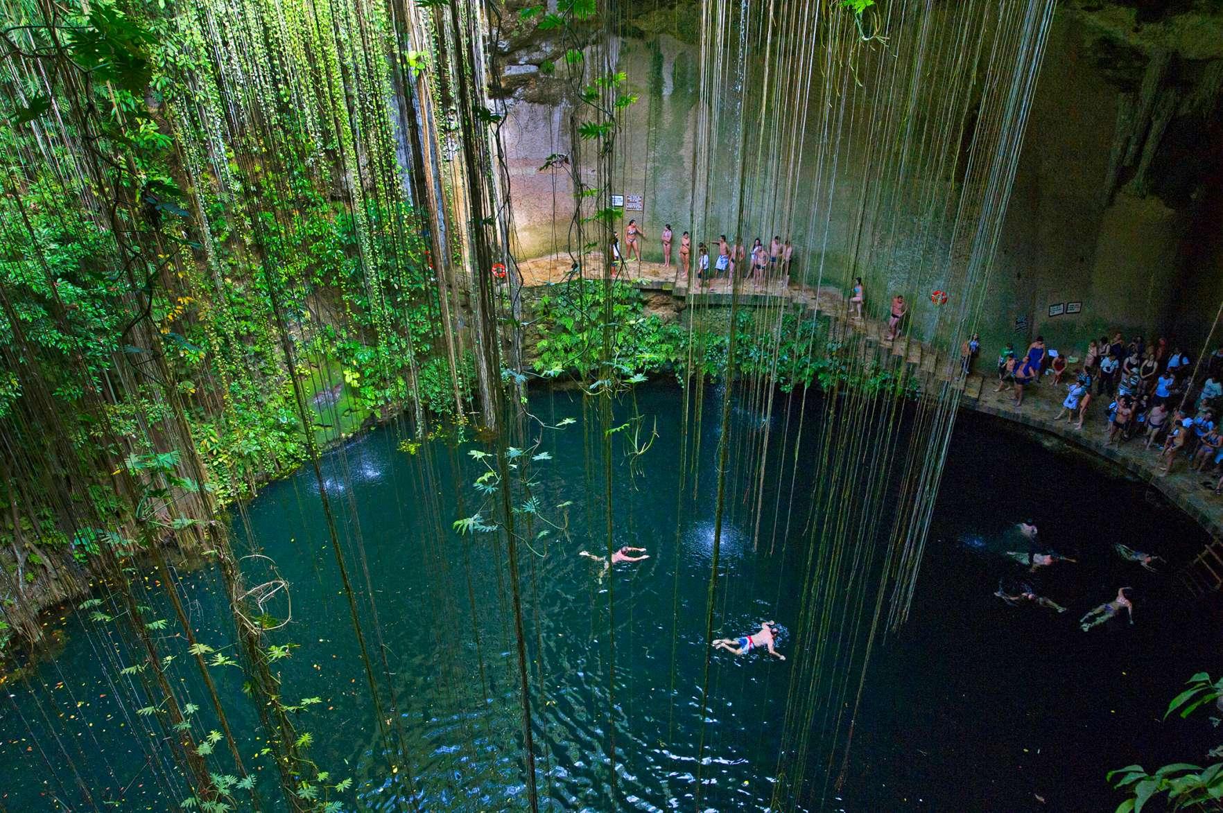 Tourists swimming in Ikil cenote on Yukatan peninsula in Mexico