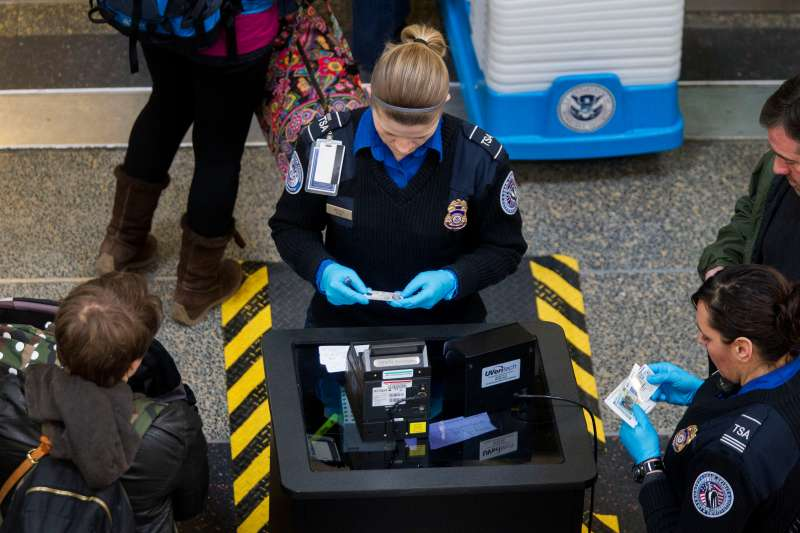 Transportation Security Administration (TSA) officers check passenger's identification at a security checkpoint at Ronald Reagan National Airport (DCA) in Washington, D.C., U.S., on Wednesday, Feb. 25, 2015. Financing for the U.S. Department of Homeland Security (DHS) is set to lapse after Friday and the agency would face a partial shutdown unless Congress provides new money. More than 200,000 government employees deemed essential at DHS, including TSA officers, would still have to report to their posts, even though their pay would stop unless Congress finds a solution. Photographer: Andrew Harrer/Bloomberg via Getty Images