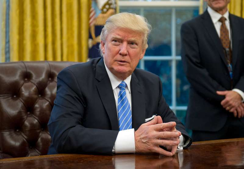 President Donald Trump prepares to sign three Executive Orders in the Oval Office on January 23, 2017.