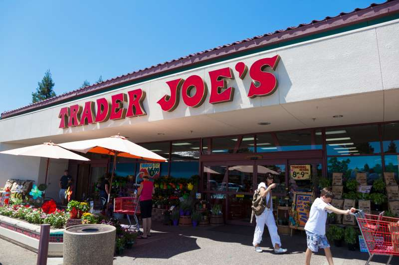 Shoppers going in and out of Trader Joe's grocery store on a sunny summer day.