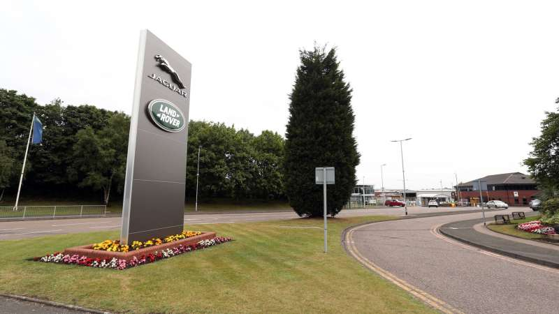 The Jaguar and Land Rover company logos sit on a sign at the entrance to Tata Motors Ltd.'s Jaguar Land Rover vehicle manufacturing plant in Solihull, U.K., on Wednesday, July, 15, 2015. Jaguar Land Rover, the U.K. luxury-car unit of Tata Motors Ltd., cut its sales targets and prices in China amid slowing demand in the world's largest auto market. Photographer: Chris Ratcliffe/Bloomberg