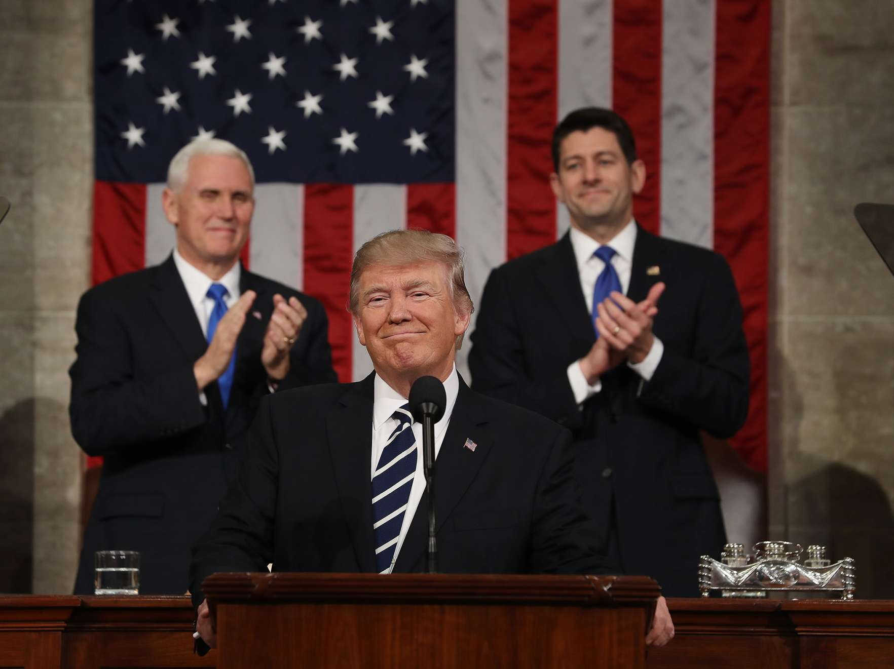 U.S. President Donald Trump, center, smiles as U.S. Vice President Mike Pence, left, and U.S. House Speaker Paul Ryan, a Republican from Wisconsin, applaud during a joint session of Congress in Washington, D.C., U.S., on Tuesday, Feb. 28, 2017.