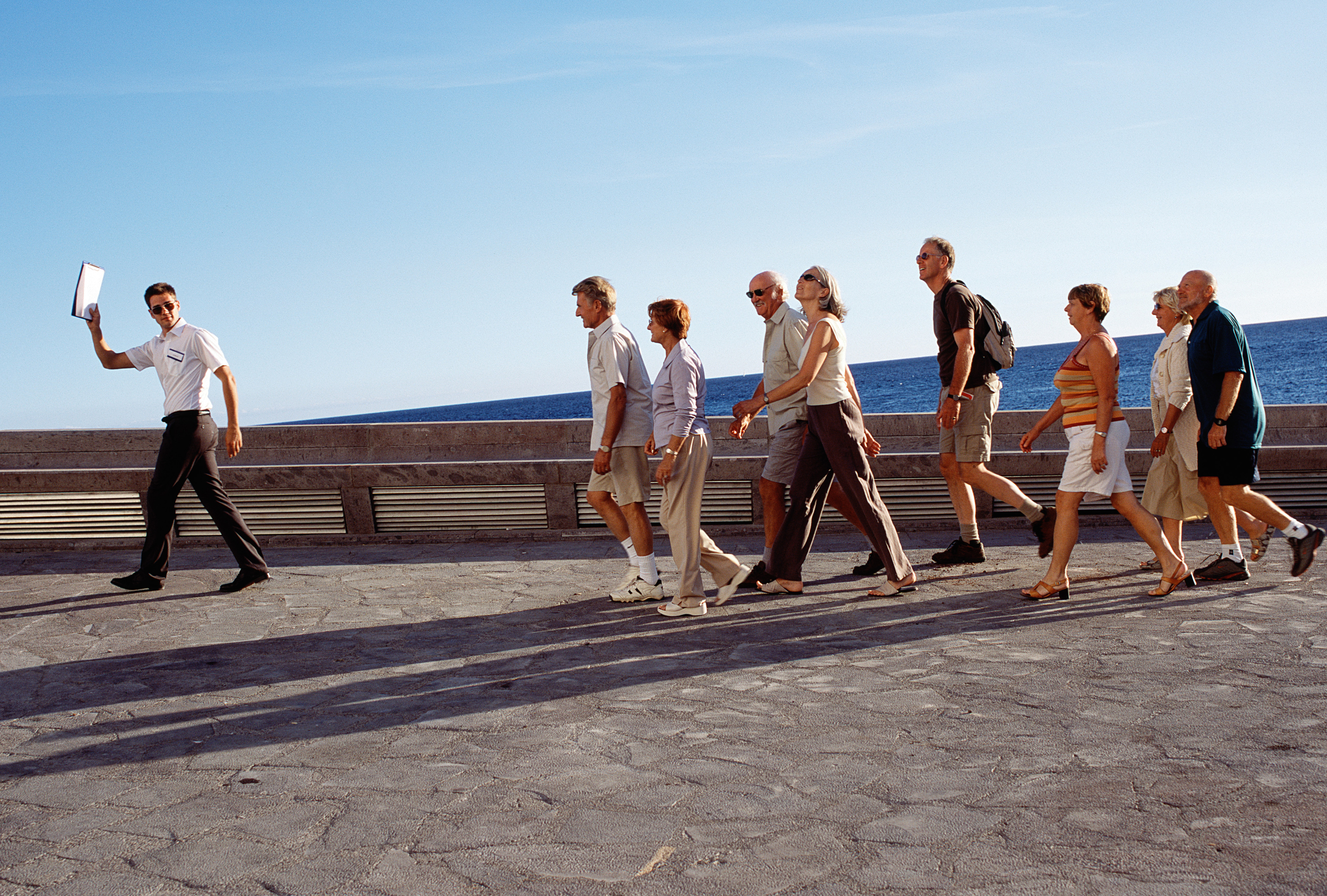 Group of tourists following male tour guide, outdoors
