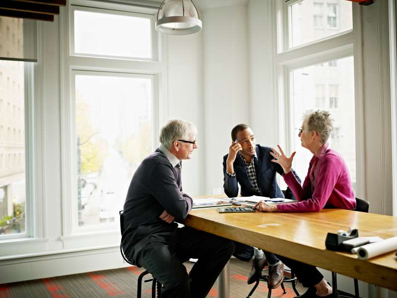 Group of three coworkers in discussion in conference room