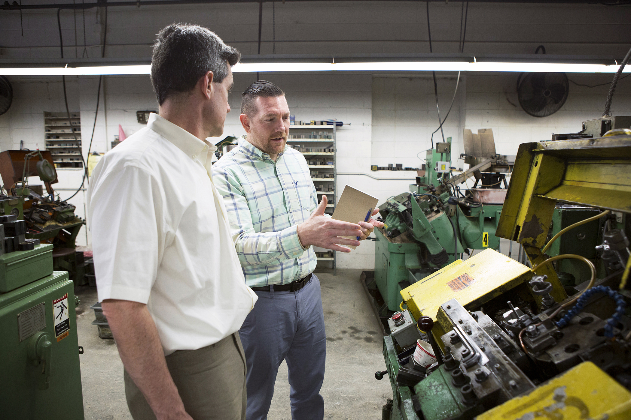 Nathan Bonds (right) talks with Christian Cowan (left), the Center Director for Polaris' Manufacturing Extension Partnership, at Rhode Island–based manufacturer Pilgrim Screw, about ways to improve their efficiencies and projects to improve their current processes and business needs. They make screws used only by the Aviation Industry.