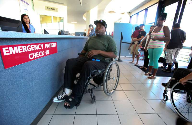 Nikita Hendrix, center (in wheelchair), waits to be treated for a pressure sore on his foot, during a visit to the emergency room at Long Beach Memorial Hospital on August 13, 2014.  In one of the first signs of the effects of Obamacare, most hospitals in Los Angeles County had an increase in visits to their emergency departments in the first part of 2014.