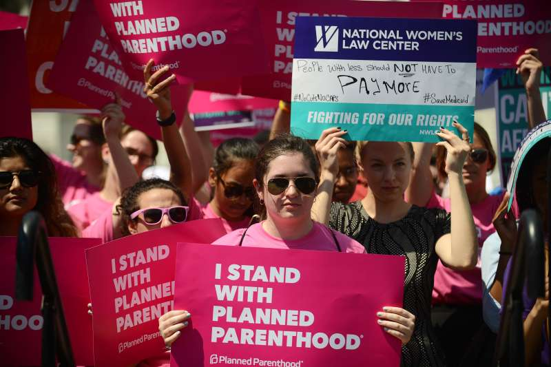 Protesters hold posters in support of Planned Parenthood at a rally to oppose the repeal of the Affordable Care Act and its replacement on Capitol Hill on June 21, 2017 in Washington, DC.