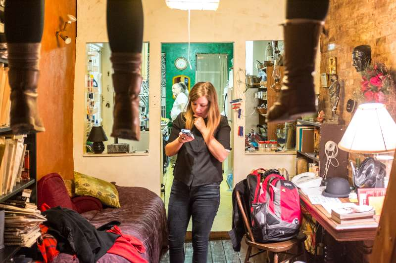 Woman checking her smart phone in a cramped small eclectic apartment in New York City