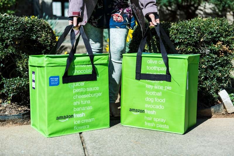 A woman picks up Amazon Fresh insulated grocery delivery bags on front porch, Fairfax, Virginia, March 2, 2017.