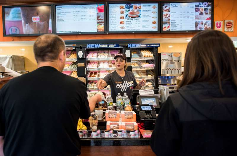 An employee helps customers at a Dunkin' Donuts Inc. location in Ramsey, New Jersey, U.S., on Thursday, May 5, 2016.
