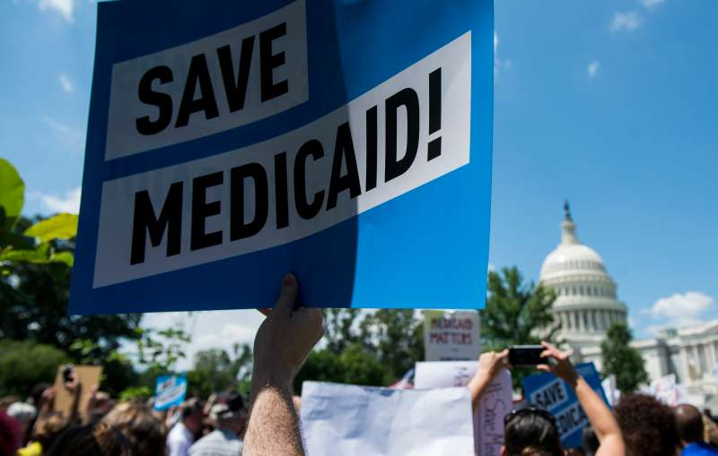 Participants hold signs during the Senate Democrats' rally against Medicaid cuts in front of the U.S. Capitol on Tuesday, June 6, 2017.