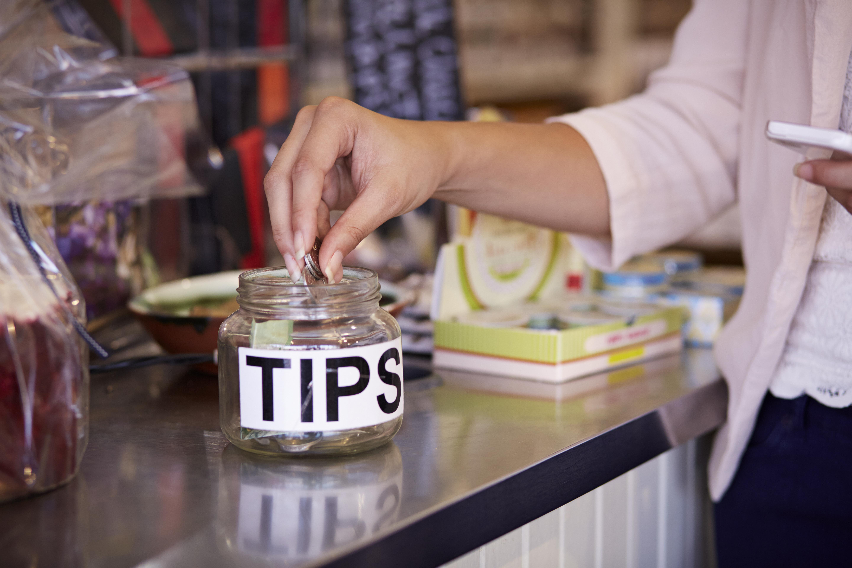 Close-up of woman tipping at café