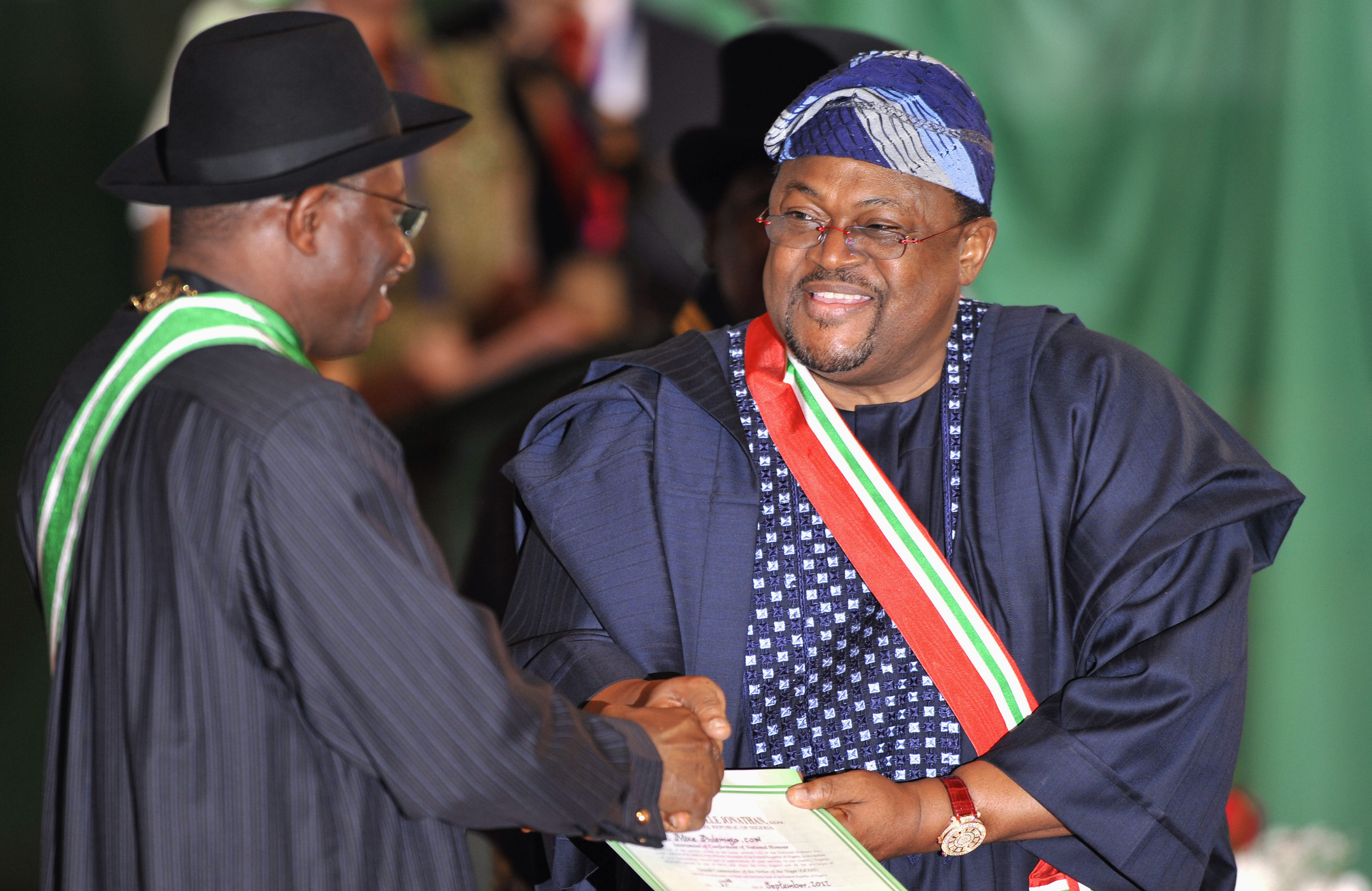 Nigeria's President Jonathan presents a national honours award to Nigeria's billionaire Adenuga at an investiture ceremony in the capital Abuja